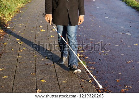 A blind person walking on the street using a red and white walking stick. #1219320265
