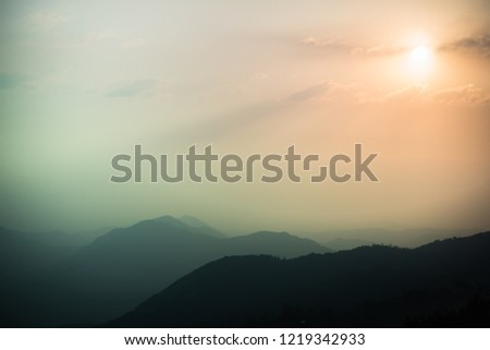 Beautiful pale pastel colors of spooky foggy mountainous landscape. Pale mauve pink to grey teal blue abstract mountain and sky scape background. Sequoia National Park forested hills in misty light. #1219342933
