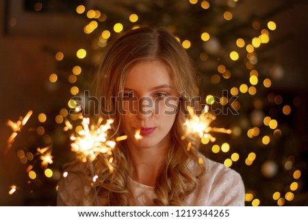 Blonde womal fascinated by sparklers #1219344265