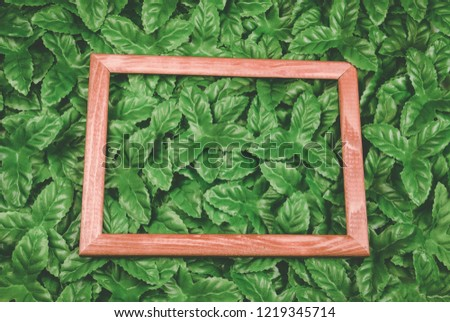 Wooden frame around green leaves on background. Blank for advertising card or invitation. #1219345714
