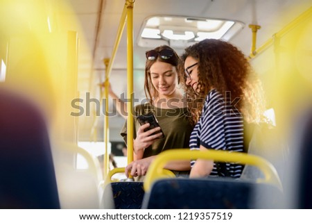 Two girlfriends standing in a bus and talking. Traveling together to the school. Looking at the telephone and having fun. #1219357519