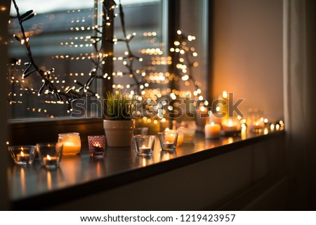 hygge, decoration and christmas concept - candles burning in lanterns on window sill and festive garland string at home Royalty-Free Stock Photo #1219423957