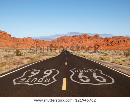 Route 66 pavement sign with Mojave desert red rock mountains. Royalty-Free Stock Photo #121945762