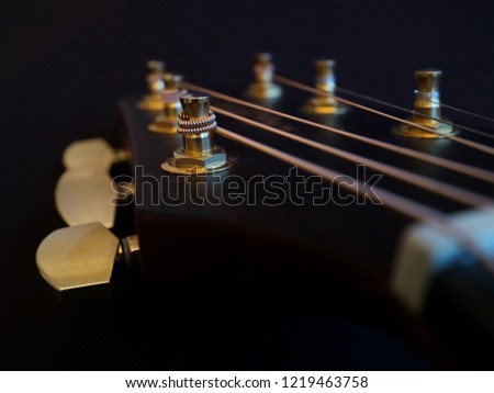 Close up of head of acoustic guitar with dark background and its string  #1219463758