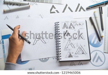 Graphic designer drawing sketch design creative Ideas draft Logo product trademark label brand artwork. Graphic designer studio Concept. #1219465006