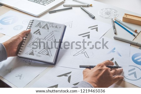 Graphic designer drawing sketch design creative Ideas draft Logo product trademark label brand artwork. Graphic designer studio Concept. #1219465036