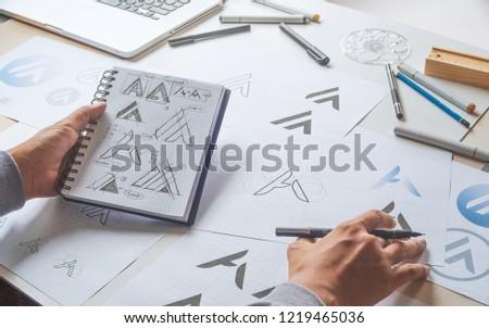 Graphic designer drawing sketch design creative Ideas draft Logo product trademark label brand artwork. Graphic designer studio Concept. #1219465036