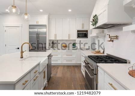 White Kitchen Detail in New Luxury Home: Includes Oven, Range,Stainless Steel Refrigerator, Hood, Cabinets, and Countertop #1219482079