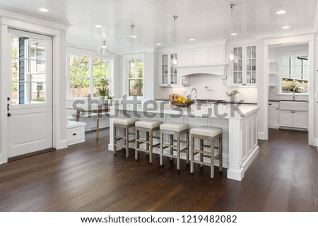 Beautiful White Kitchen in New Luxury Home. Features large island, eating nook, hardwood floors, and second sink. #1219482082