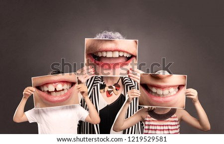 grandma with grandchild holding a picture of a mouth smiling on a gray background