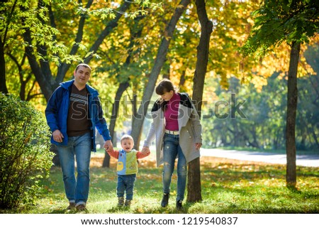 Beautiful young family on a walk in autumn forest on maple yellow trees background. Father and mother hold son on hands. Happy family leisure together concept. #1219540837