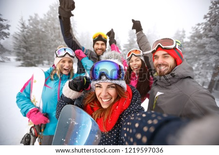 Cheerful friends with hands up on skiing #1219597036