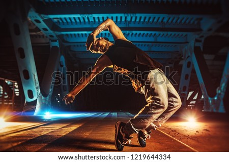 Young cool man break dancer on urban bridge with cool and warm lights background. Tattoo on body. #1219644334