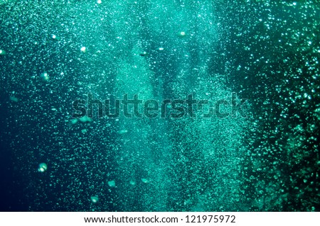The picture shows underwater bubbles which raise from the depth of blue sea