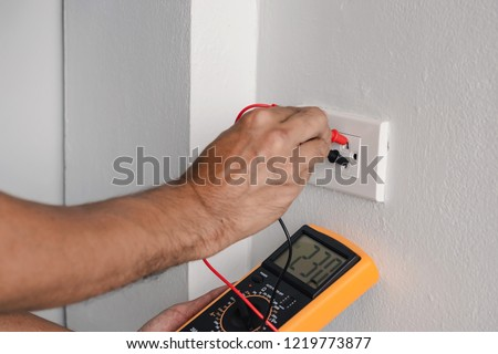 Electrician is using a digital meter to measure the voltage at the power outlet in on the wall. #1219773877