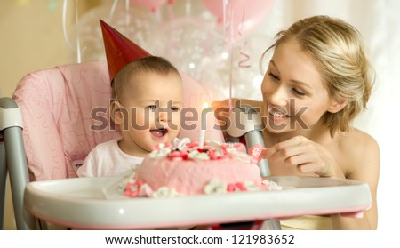one-year-old little girl with  mammy solemnize birthday, happy laughter, horizontal photo