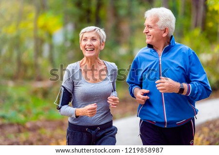 Smiling senior couple jogging in the park #1219858987
