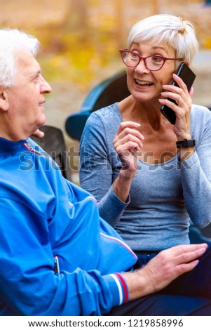 Smiling senior active couple sitting on the bench talking #1219858996