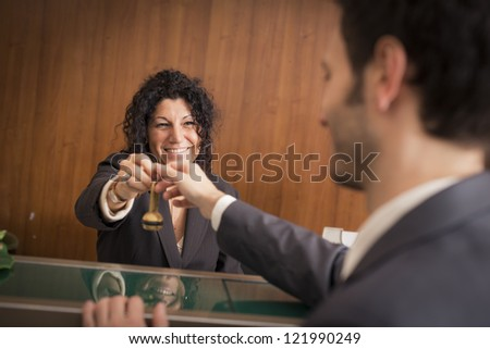 Businessman with key at the hotel reception #121990249