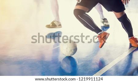 Indoor soccer sports hall. Football futsal player, ball, futsal floor. Sports background. Youth futsal league. Indoor football players with classic soccer ball. #1219911124