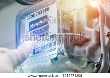 Energy concept. Hand is touching the transformer with copy space. Incorrect energy detection method. Watthour meter of electricity for use in home appliance. Electronics #1219971205