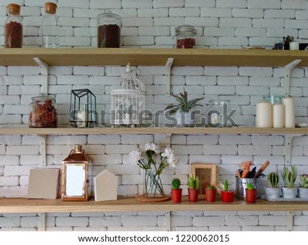 Miscellaneous on the wall shelf. Things on the brick wall shelf. Shelves on a white brick wall. Decorative items on the shelf. Interior design of wall. Royalty-Free Stock Photo #1220062015