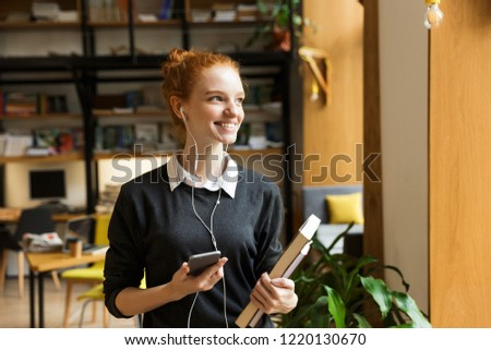 Image of beautiful cheerful happy redhead lady student posing indoors in library holding books listening music with earphones using mobile phone. #1220130670