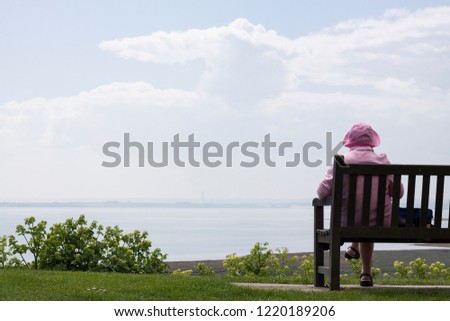 An Old Retired English woman in pink clothes sitting on the bench and enjoying seascape view. #1220189206