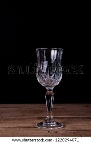 Elegant liqueur glass on wooden table with black wall background #1220294071