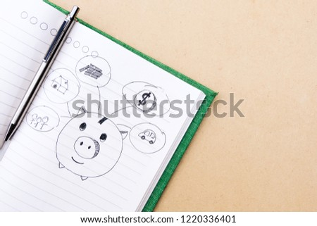 Drawn sketchy piggy bank and money related icons on lined notebook paper background. Save and investment money for prepare in the future - concept of saving money. #1220336401