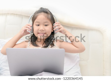 Cute girl play laptop and listening music from headphone, education concept #1220364145