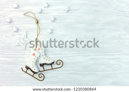 christmas wooden background with small ice skates and white stars. flat lay