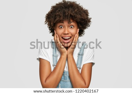 Emotions and reaction concept. Happy emotional lady with dark healthy skin, keeps both hands on cheeks, gazes with pleased surprised expression, dressed in stylish clothes, isolated on white wall #1220402167