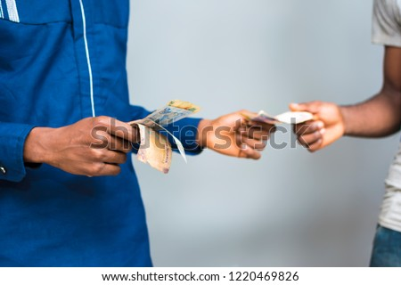 picture of two people's hands exchanging money. a black man giving money to someone