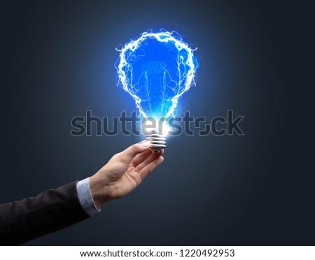 Hand holding shiny light bulb on dark background. New idea concept #1220492953