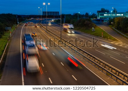 Fast moving traffic speeds along the M5 motorway in Worcestershire during the evening rush hour, leaving light trails and streaks of illumination as it moves #1220504725