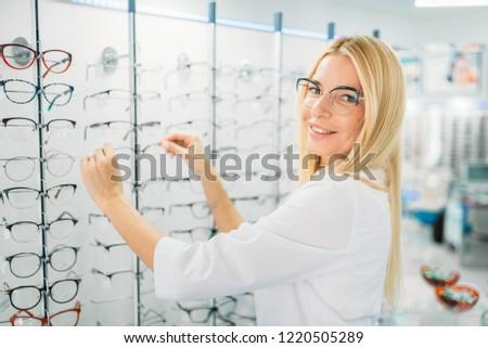 Female optometrist shows glasses in optics store #1220505289