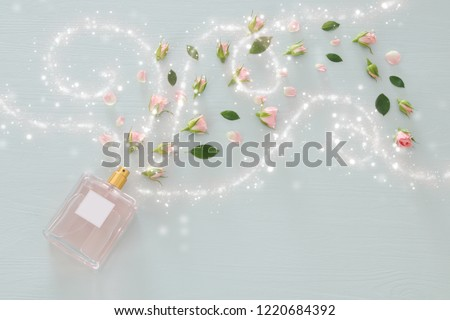 Top view image of perfume bottle with rose petals flowers over pastel blue background. Floral scent concept #1220684392