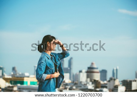 Portrait of a relaxed Asian woman looking forward at the horizon cityscape in the background with her hand on the forehead- copy space #1220703700