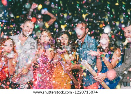 Happy friends doing party throwing confetti in the club - Millennials young people having fun celebrating in the nightclub - Nightlife, entertainment and festive holidays concept  #1220715874