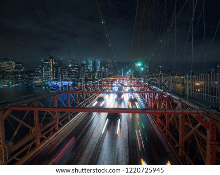 Traffic cars over the Brooklyn Bridge. Against the night cityscape NYC #1220725945