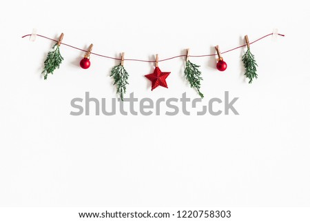 Christmas composition. Garland made of red balls and fir tree branches on white background. Christmas, winter, new year concept. Flat lay, top view, copy space #1220758303