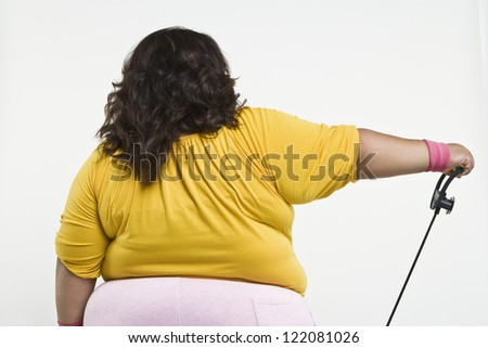 Rear view of an obese woman exercising isolated over white background #122081026