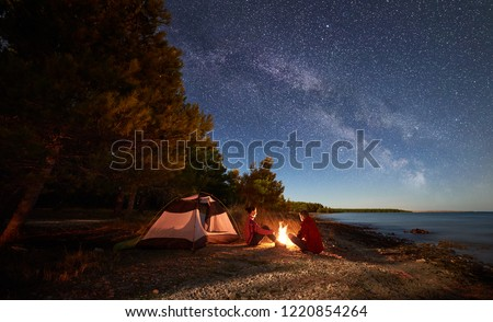 Night camping on shore. Man and woman hikers having a rest in front of tent at campfire under evening sky full of stars and Milky way on blue water and forest background. Outdoor lifestyle concept #1220854264