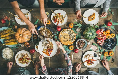 Traditional Thanksgiving day celebration party. Flat-lay of Friends or family eating different snacks and roast turkey or chicken at Festive Christmas table, top view #1220868844