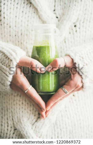 Winter seasonal smoothie drink detox. Female in knitted sweater holding bottle of green smoothie or juice making heart shape with her hands. Clean eating, weight loss, healthy dieting food concept #1220869372