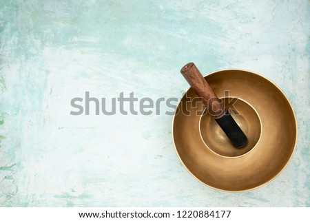 Two singing bowls stand one on the other on an artistically painted background of light blue. Vintage singing bowls ready for use for healing sound massage. Top view. Royalty-Free Stock Photo #1220884177