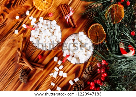 Homemade two Cocoa glasses with Marshmallows. Hot winter drink on wooden Backdrop decorated with cinamon sticks and fir branches. Top view copy space. #1220947183