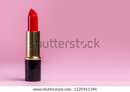 Red lipstick close-up on a pink background. Women's cosmetics for professional makeup. Copy space  #1220961346