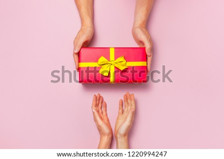 Top view of male and female hands holding red gift box with golden ribbon on pink background Flat lay. Present for birthday, valentine day, Christmas, New Year. Congratulations background copy space. #1220994247